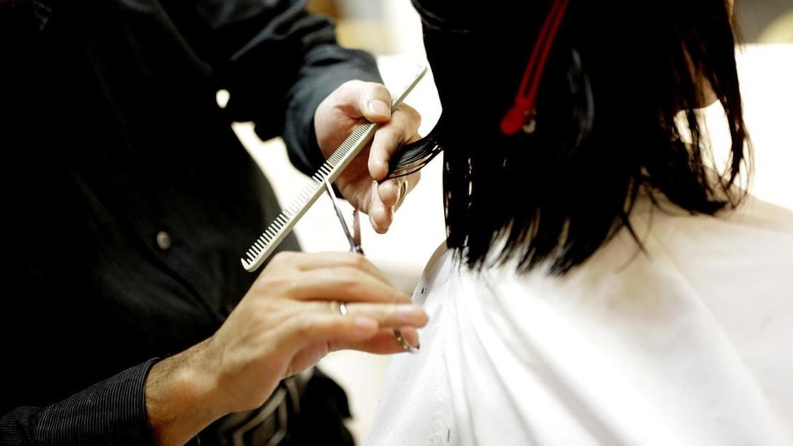 Парикмахер стрижет темные волосы