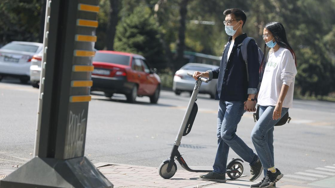 Парень и девушка идут по улице с самокатом