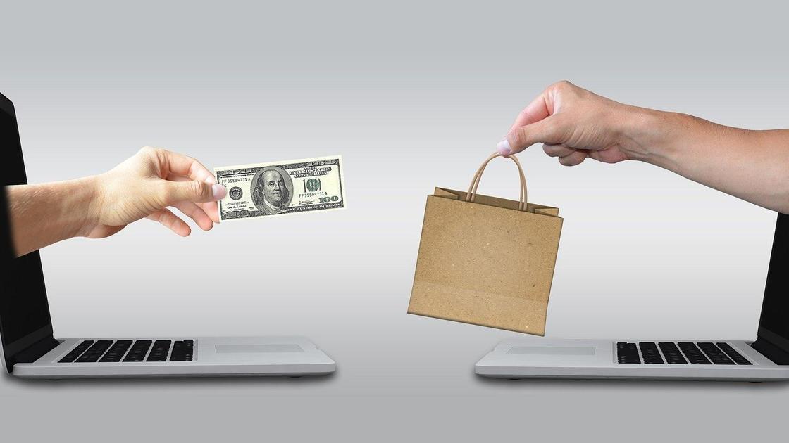 Сто долларов и бумажный пакет, передаваемые из рук в руки, на фоне ноутбуков