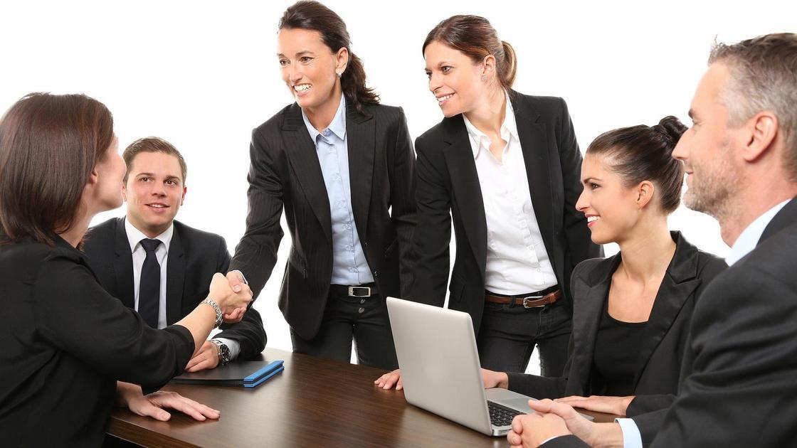 Две женщины жмут друг другу руки на совещании коллег