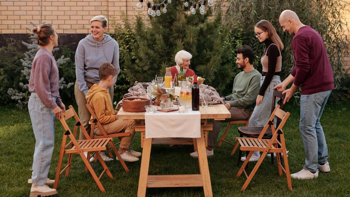 Семья из нескольких человек за столиком в саду