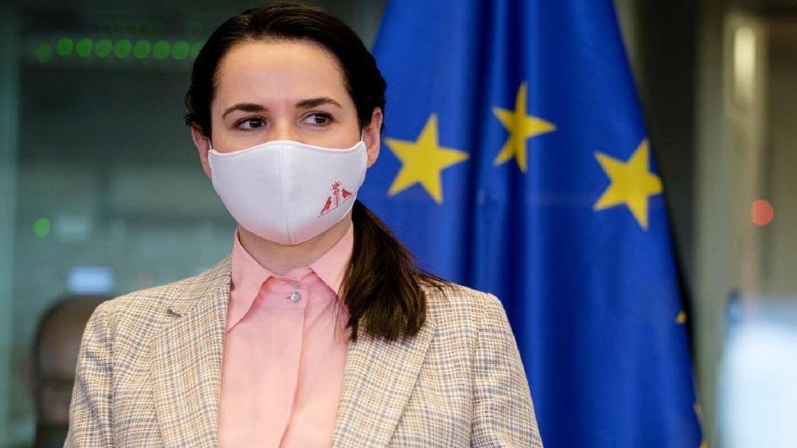 Светлана Тихановская в маске на фоне флага Евросоюза