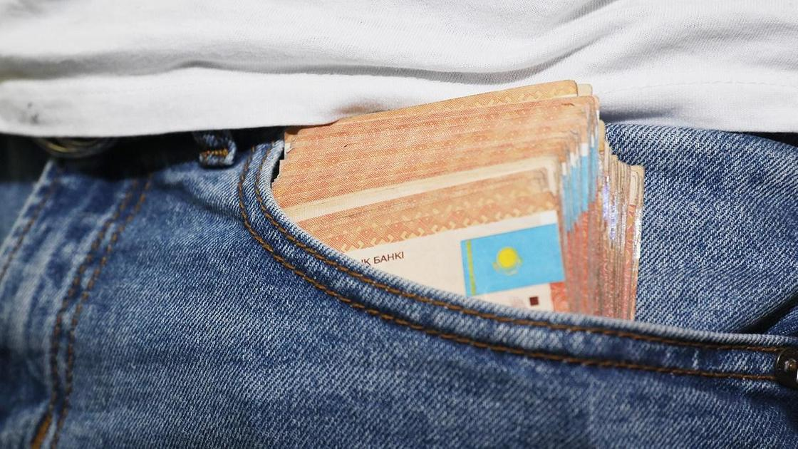 В кармане брюк лежит пачка денег