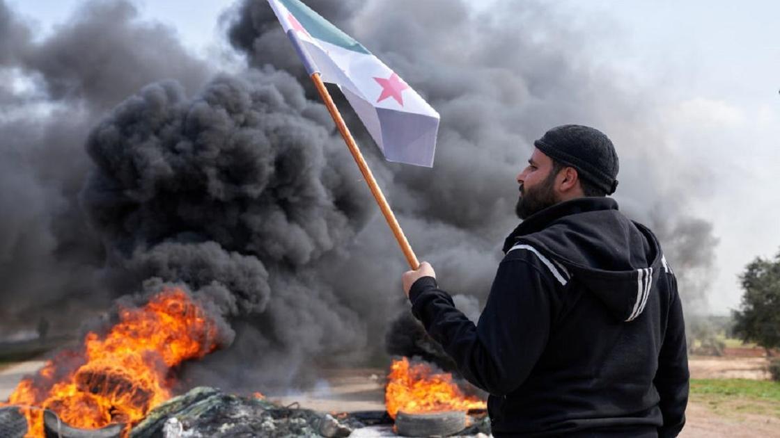 Сириец с флагом в руке на фоне подожженных шин