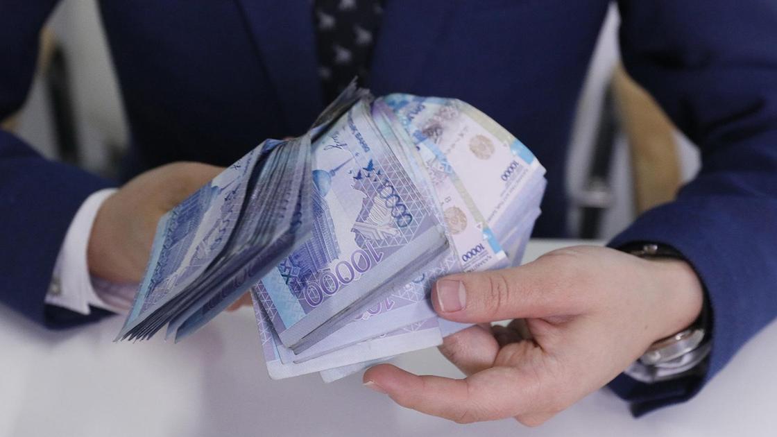 Мужчина в пиджаке держит в руках деньги