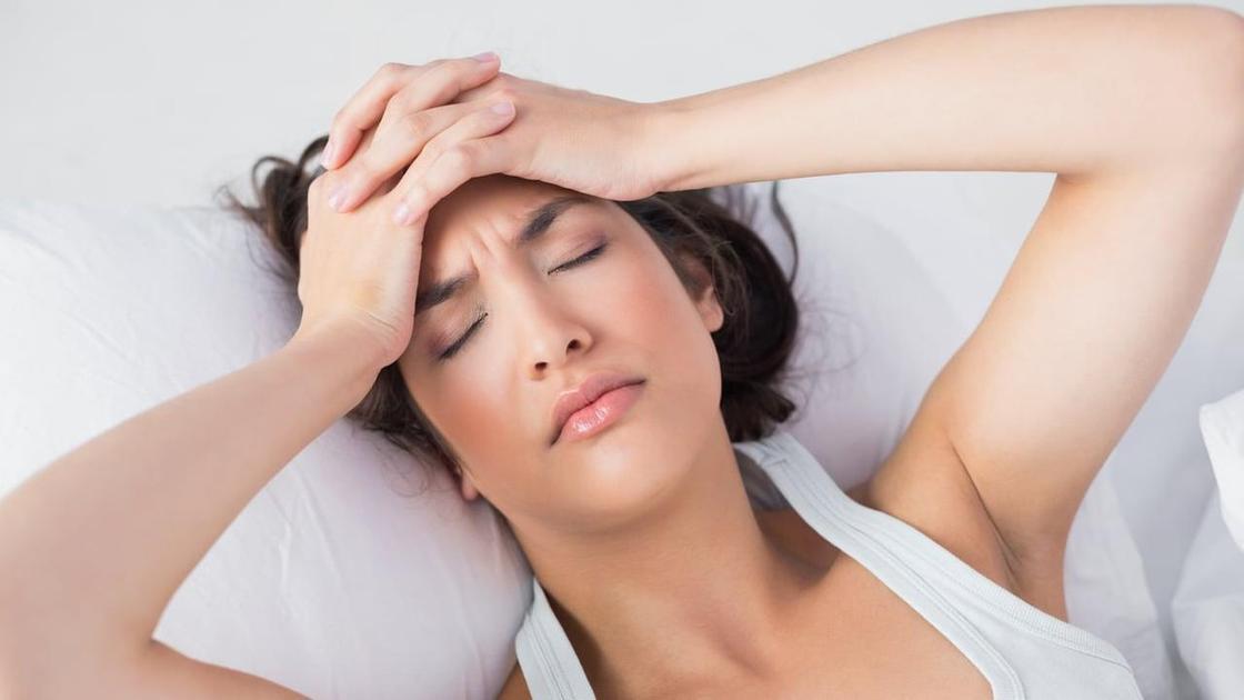 Девушка лежит на кровати и держится за голову