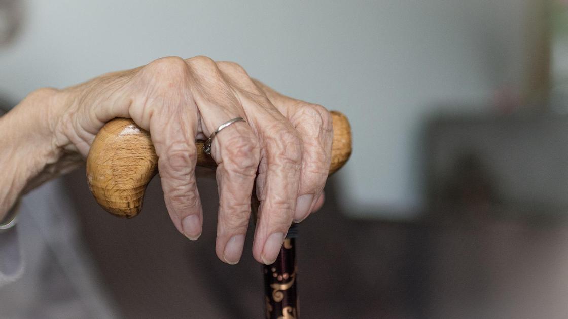 В руке пожилой женщины лежит трость