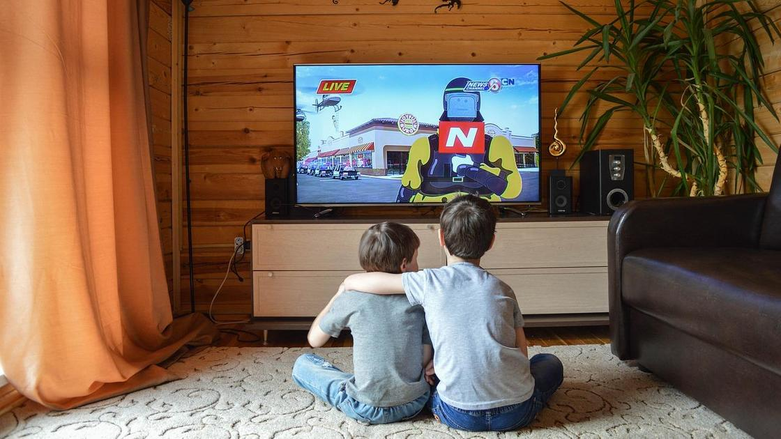 Дети смотрят мультик на телевизоре