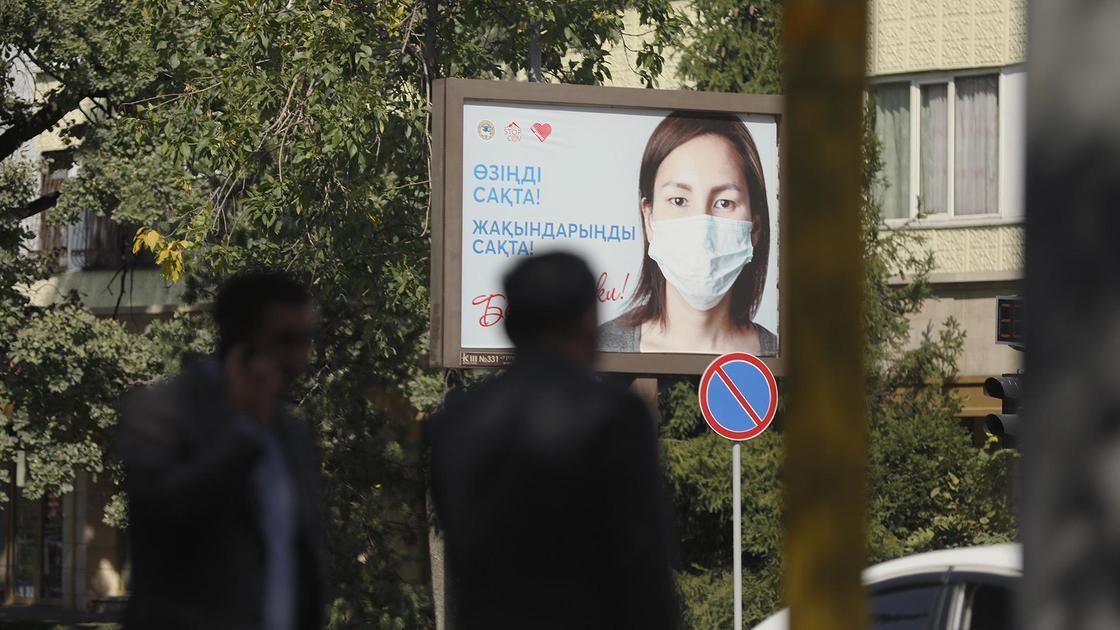 люди на фоне билборда с масками
