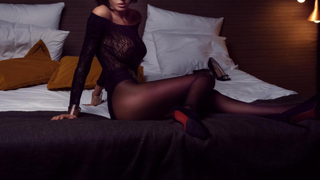 Девушка сидит на кровати в колготках и туфлях