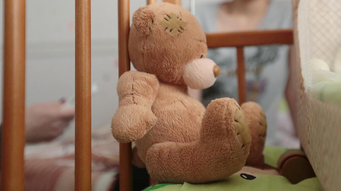 Мягкая игрушка лежит в детской кроватке на фоне матери