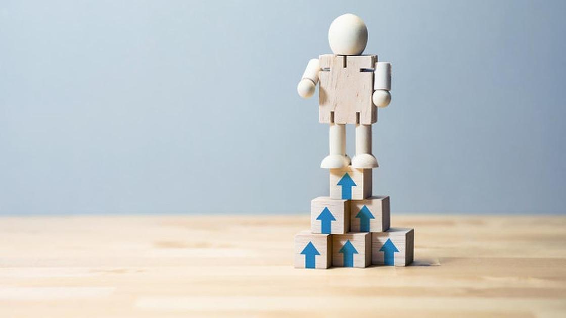 Деревянный человечек стоит на кубиках со стрелками