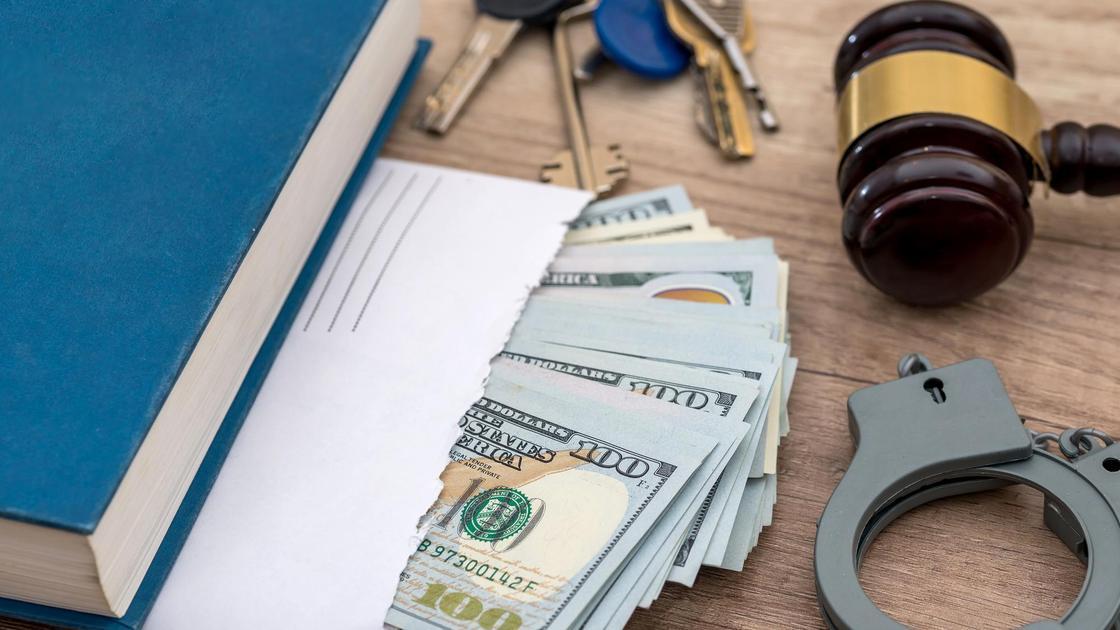 Деньги, блокнот, наручники и молоток судьи лежат на столе