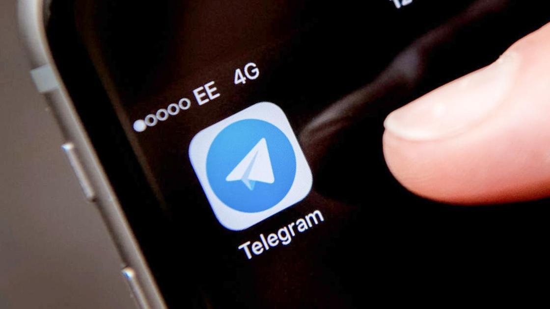 Человек нажимает пальцем руки на иконку приложения Telegram