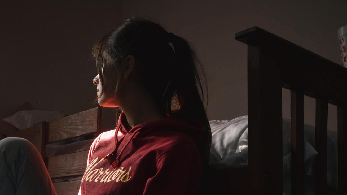 Девушка сидит около кровати