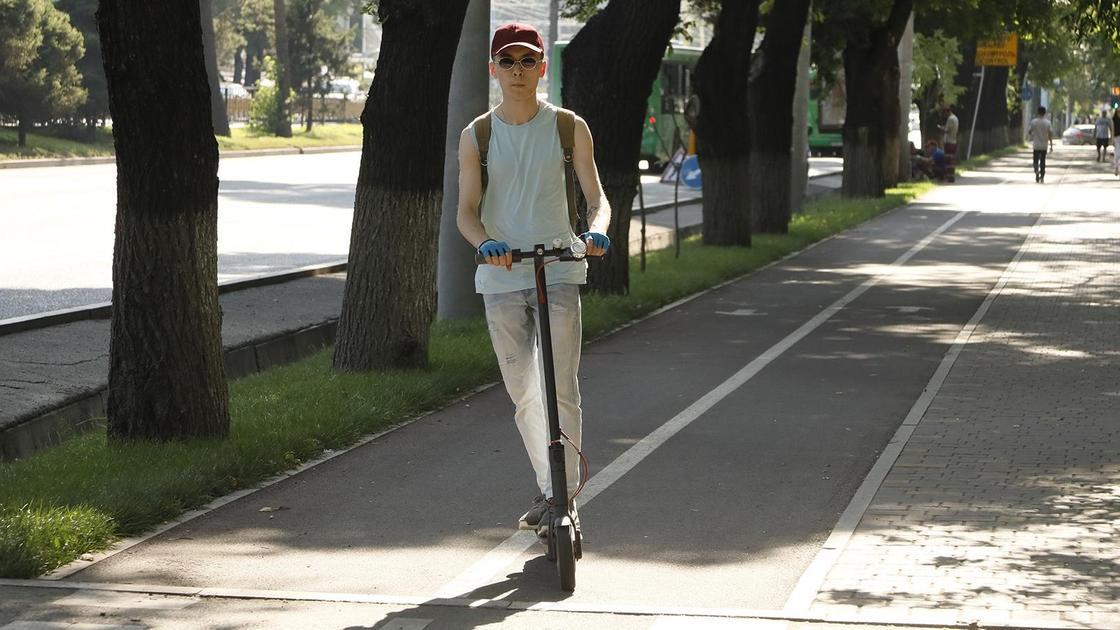 Парень на самокате едет по улице