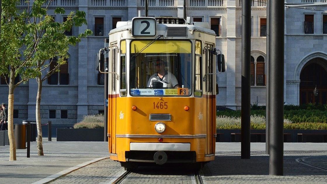 Желтый трамвай едет по рельсам