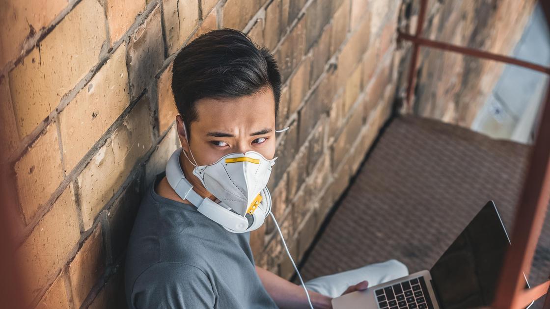 парень в маске с ноутбуком