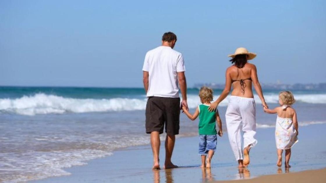 семья гуляет по пляжу