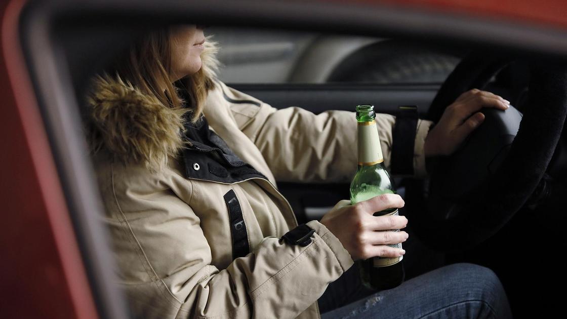 Женщина с бутылкой за рулем