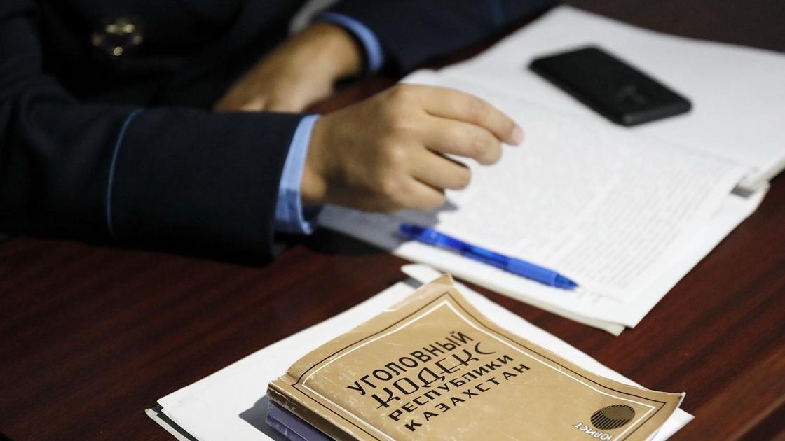 Прокурор сидит за столом в суде, а рядом лежит Уголовный кодекс Казахстана