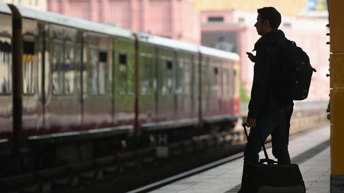 Мужчина с чемоданом на фоне отбывающего поезда