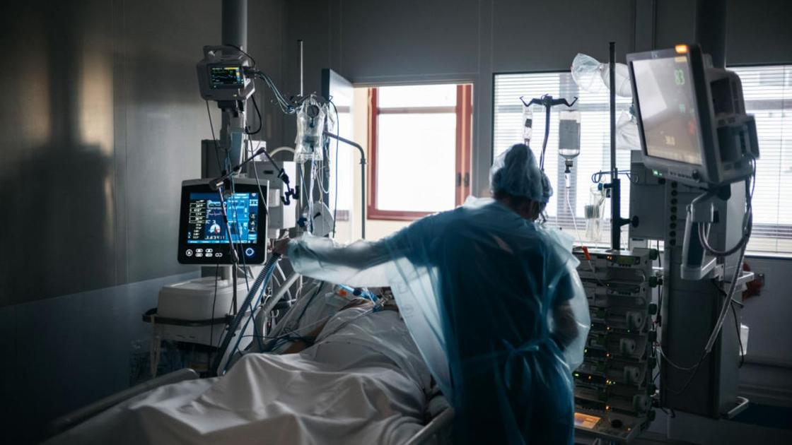 Медработник стоит возле койки с пациентом
