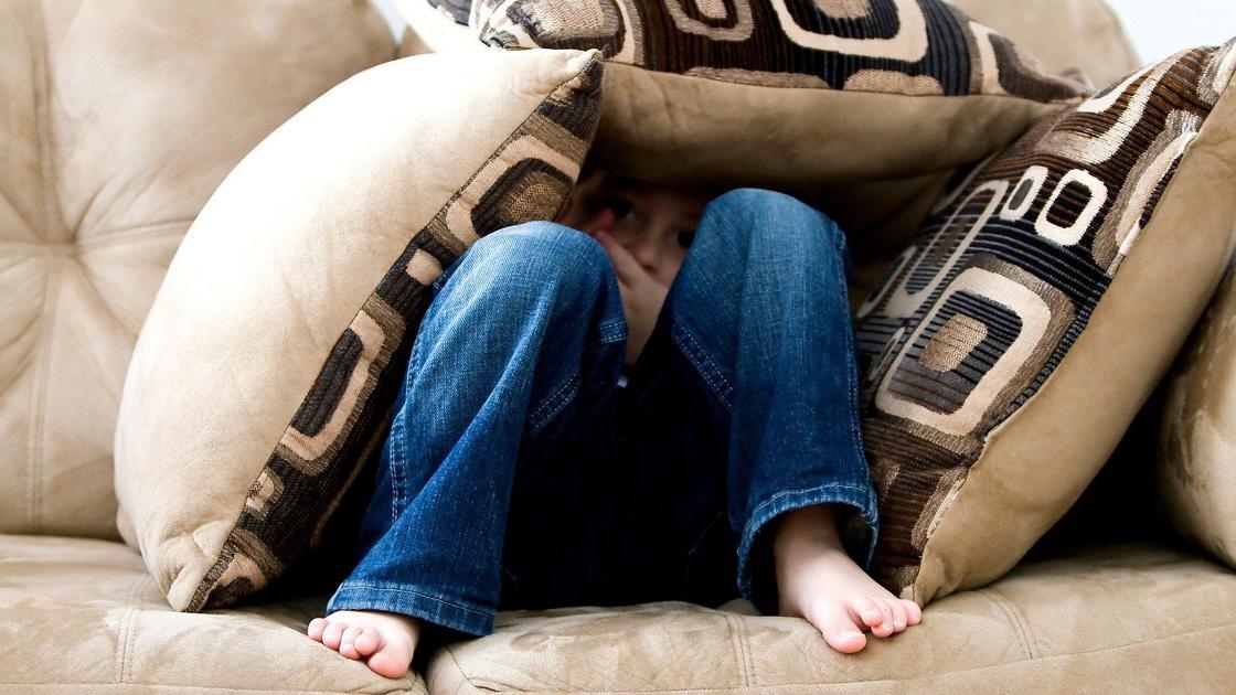 Мальчик сидит на диване, закрывшись подушками