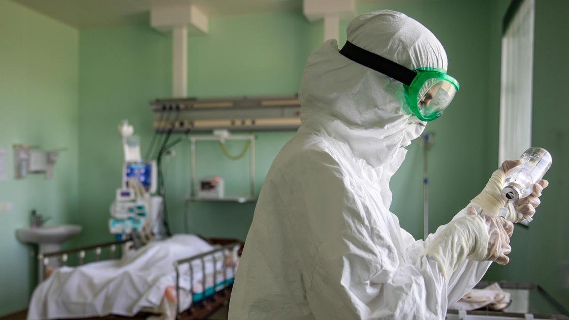Врач в защитном костюме набирает лекарство