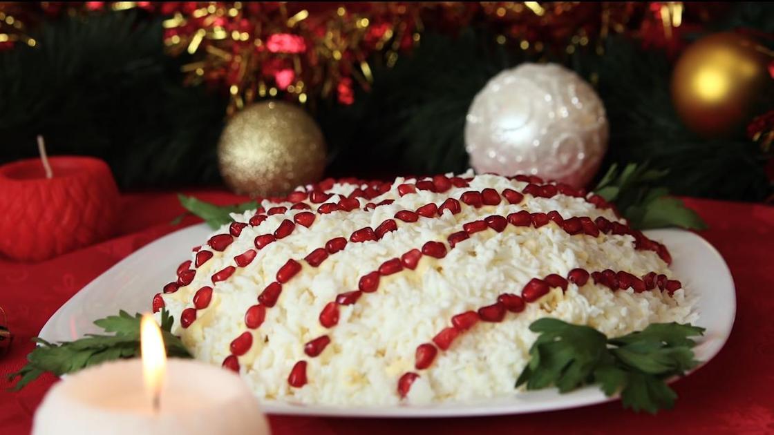 Салат на новогоднем столе рядом с елкой