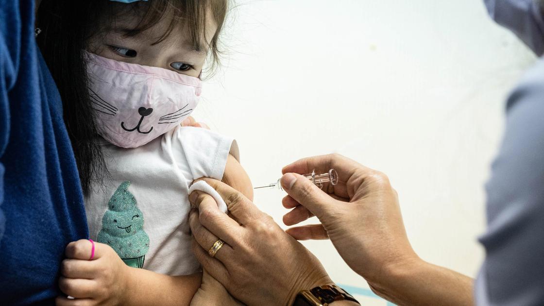Девочке в маске делают прививку