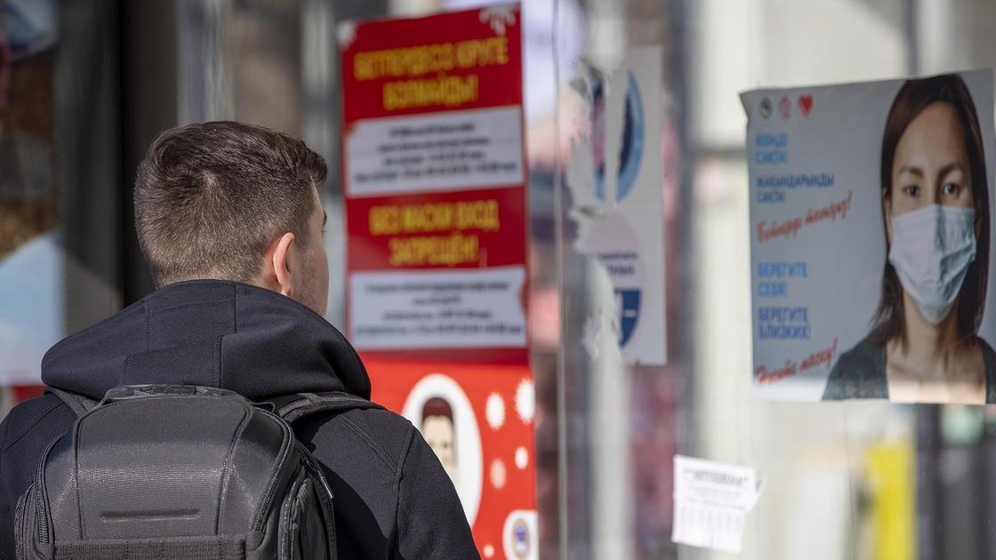 парень смотрит на баннер о коронавирусе