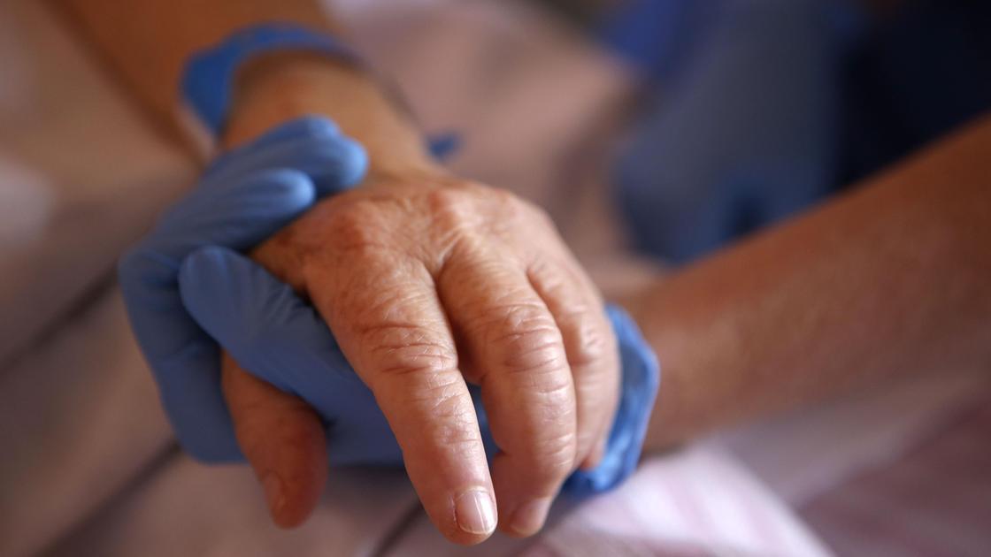 Врач держит пациента за руку