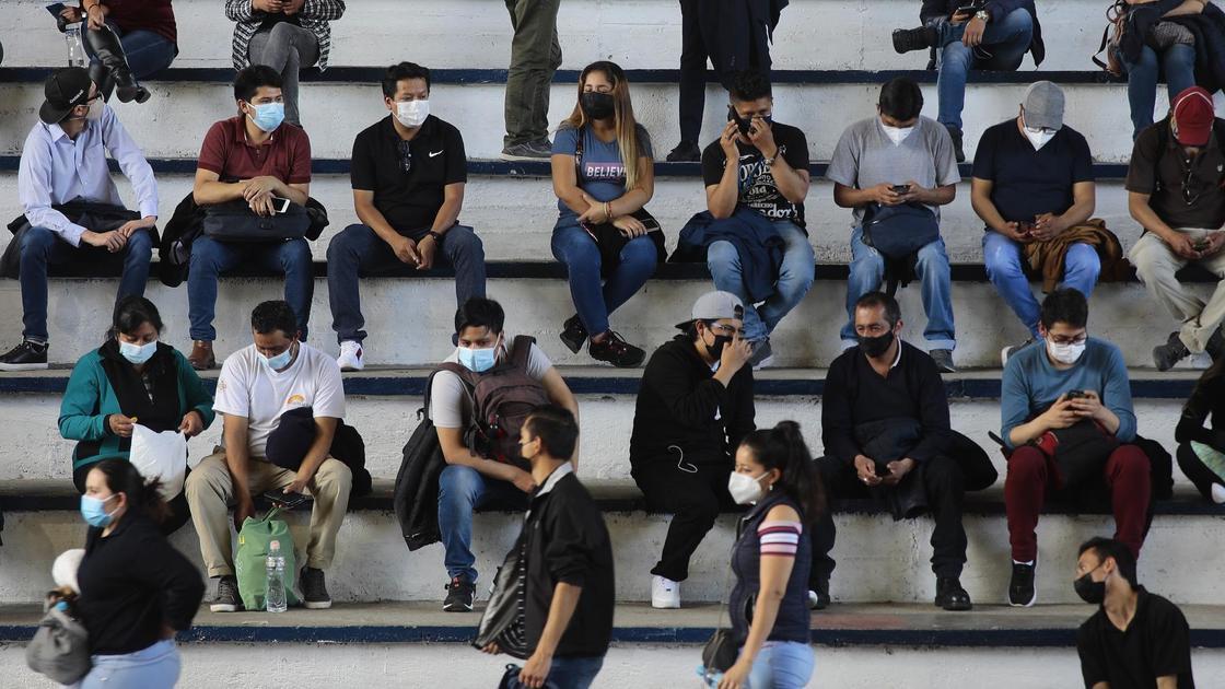 Люди ждут очереди на вакцинацию в масках