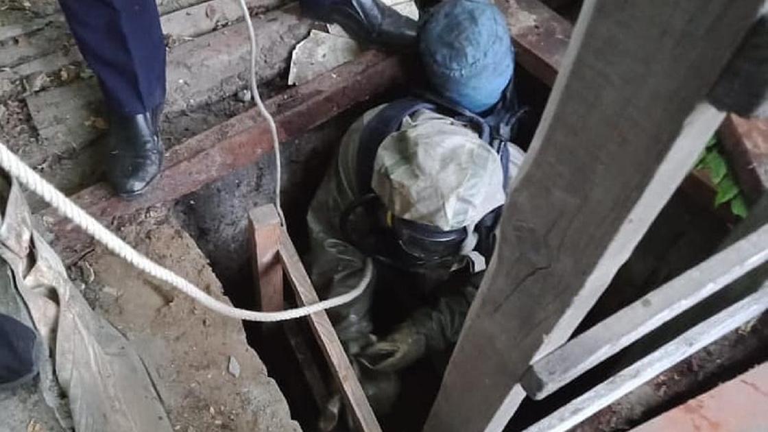 Спасатель спускается в выгребную яму