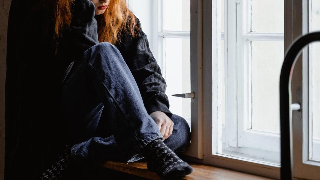 Грустная девушка сидит возле окна