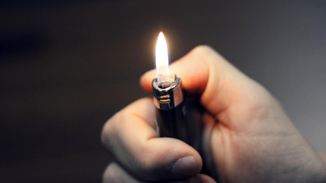 Мужчина держит в руках горящую зажигалку