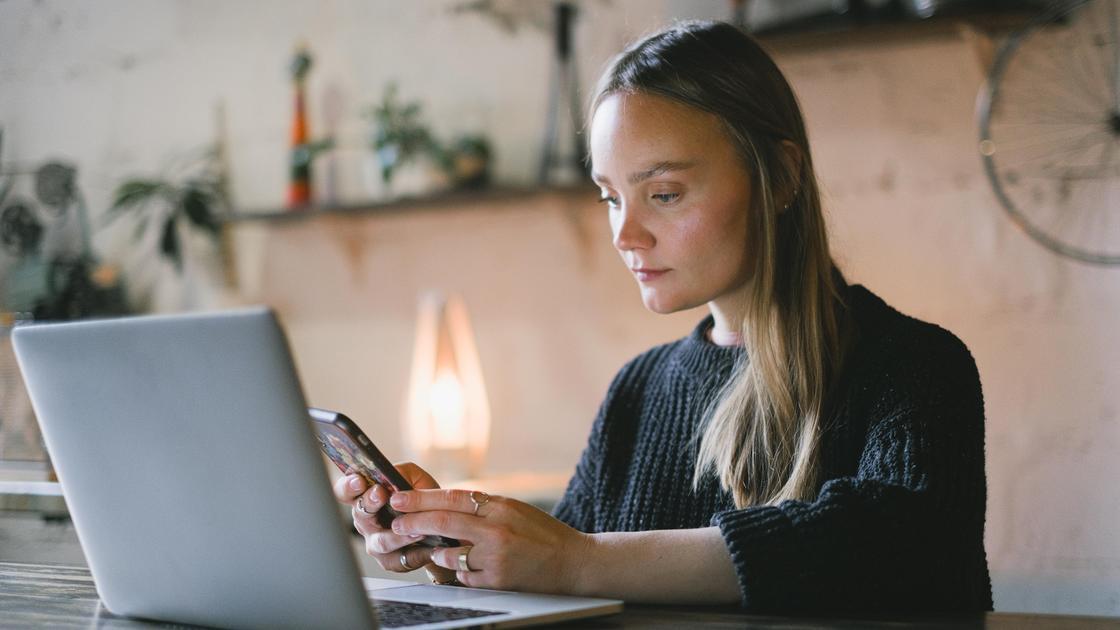 Девушка с телефоном в руках сидит за компьютером