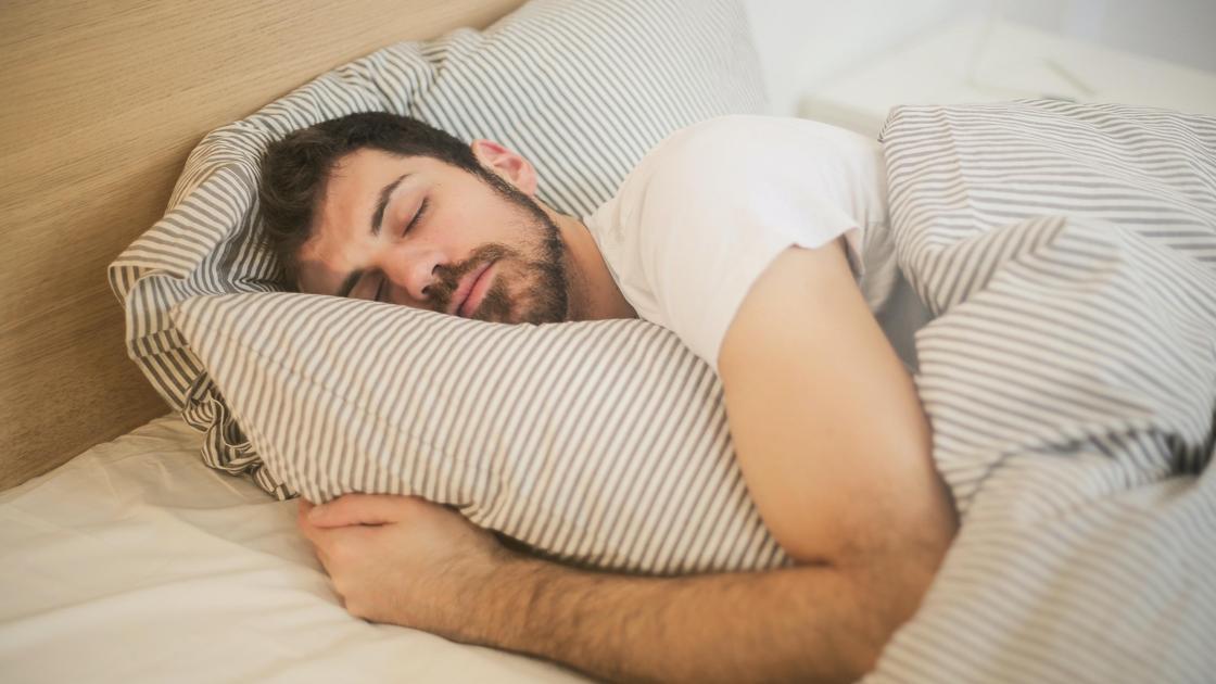 Мужчина спит на постели