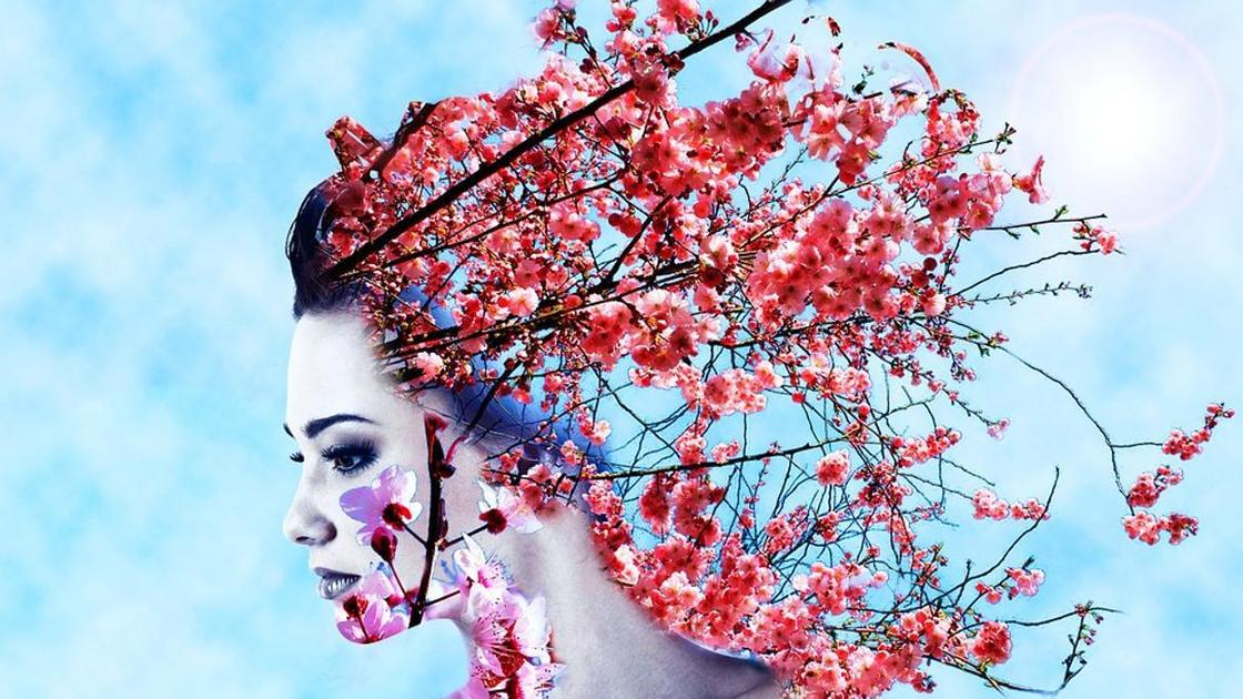 Женщина с цветами в волосах на голубом фоне