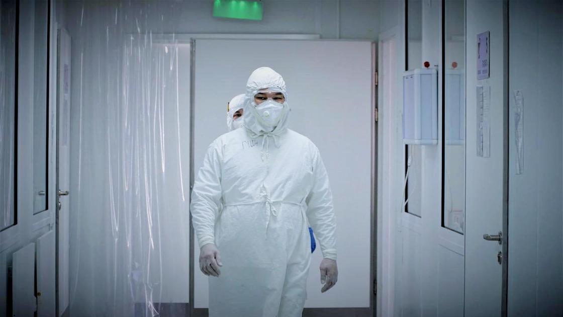 Медработница в костюме санитара идет по коридору