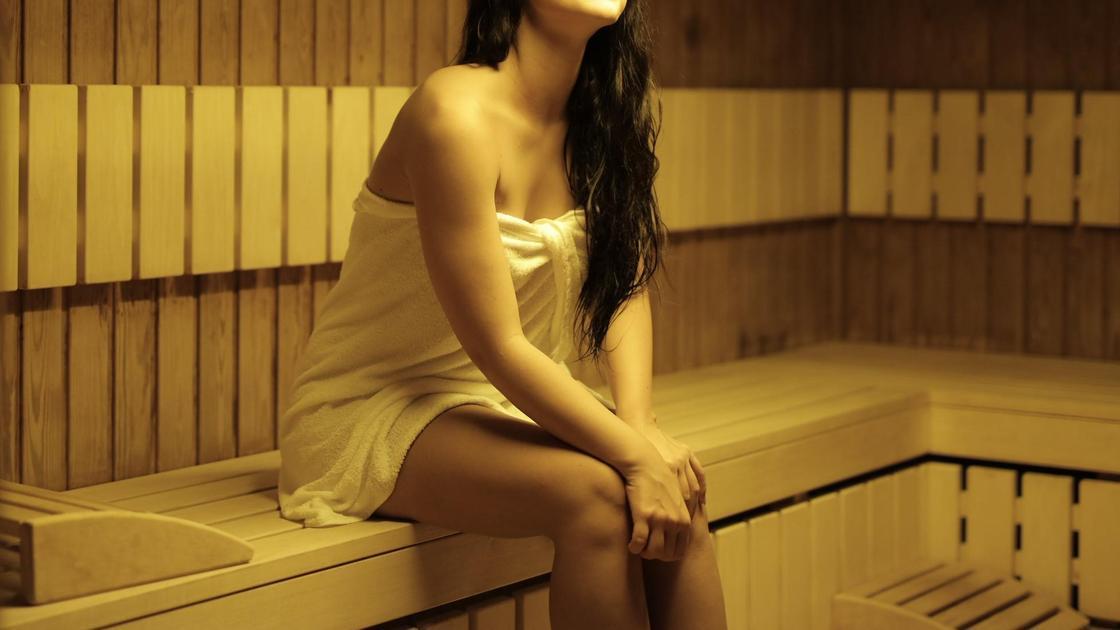Девушка сидит в парилке в сауне