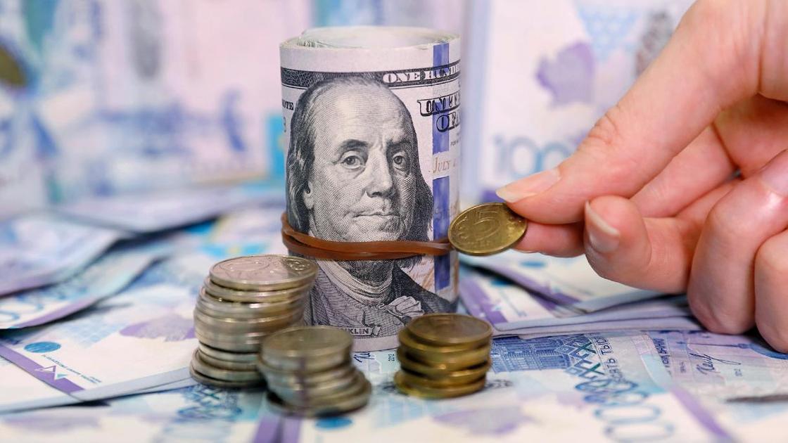 Женщина сравнивает монеты тенге с пачкой долларов