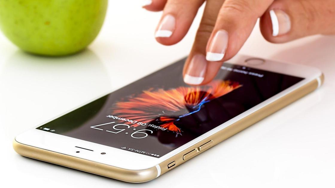 Женские пальцы касаются мобильного телефона