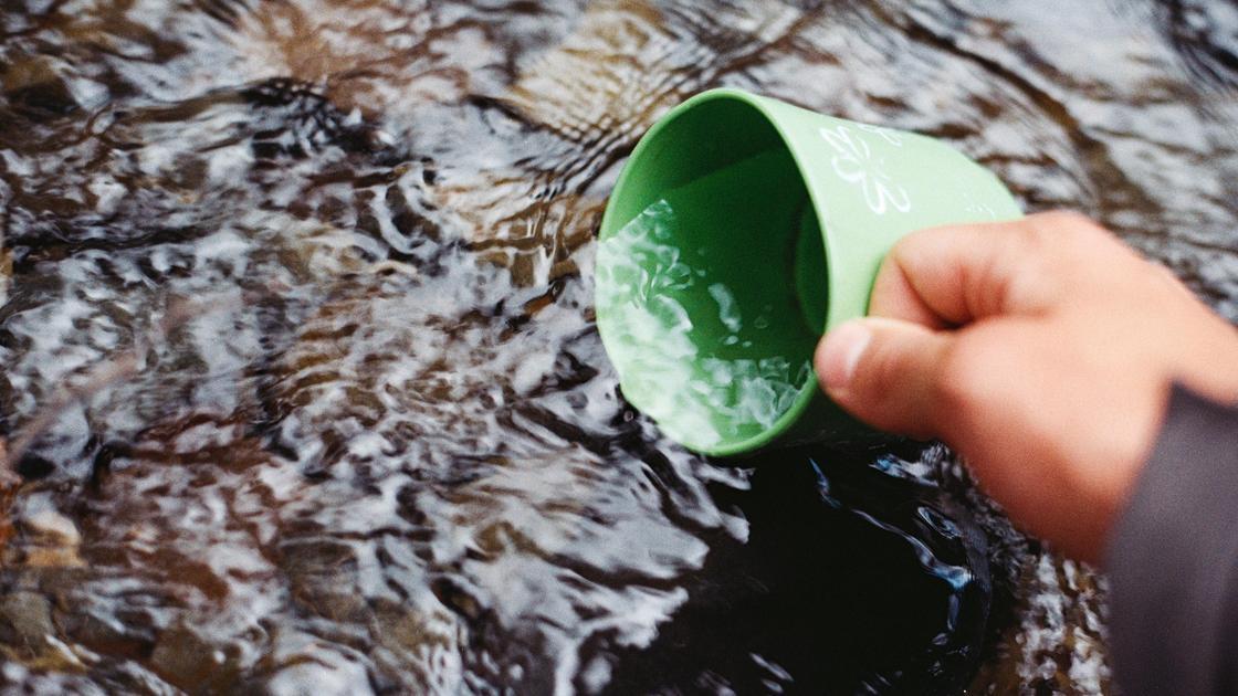 Человек набирает воду кружкой из родника
