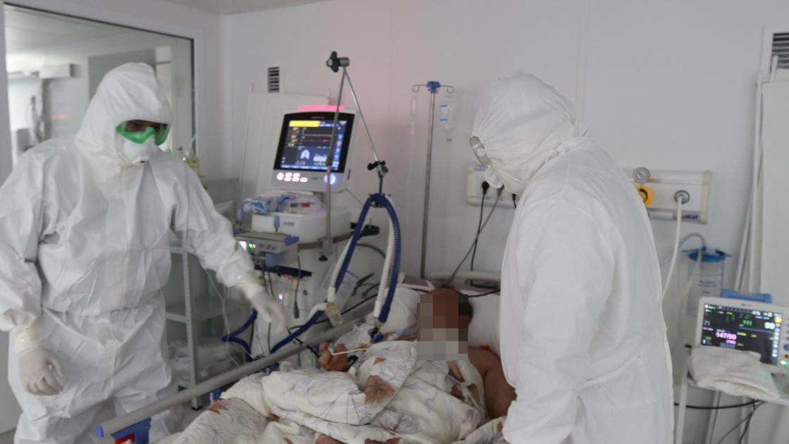 врачи стоят рядом с больным в реанимации
