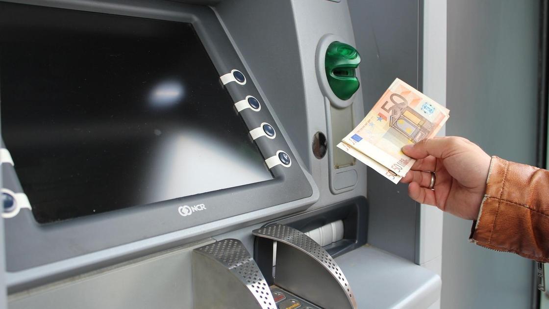 Держатель банковской карты снимает в банкомате деньги