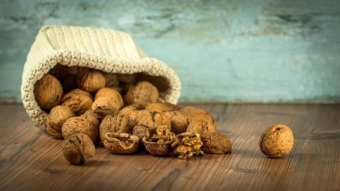 Грецкие орехи в кожуре лежат на столе