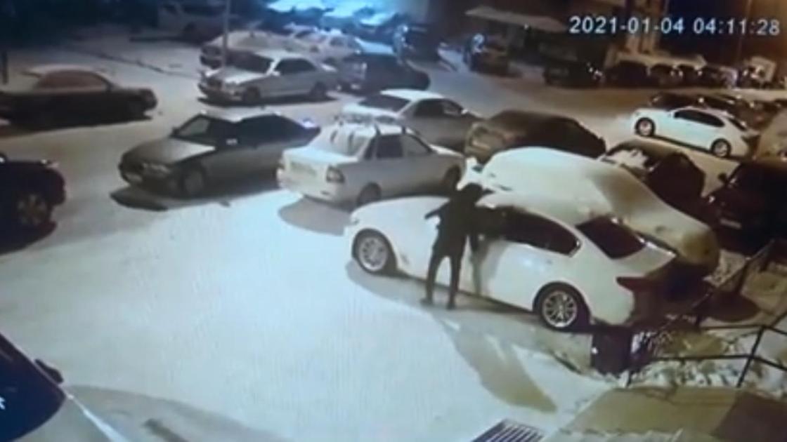 Мужчина в черной куртке дотрагивается до машины