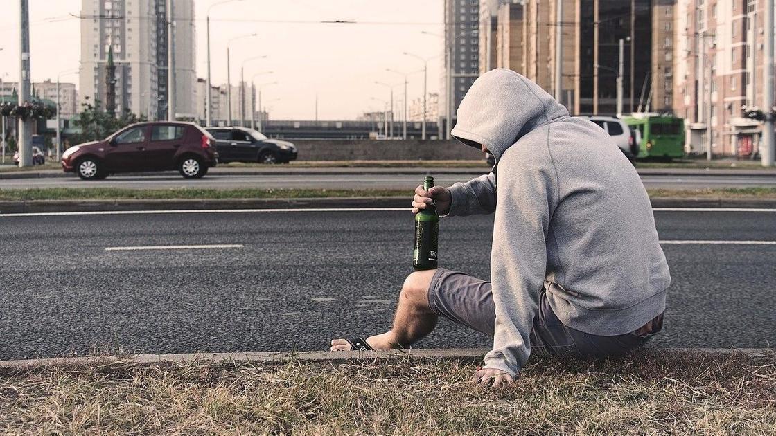 Парень с пивом сидит на проезжей части